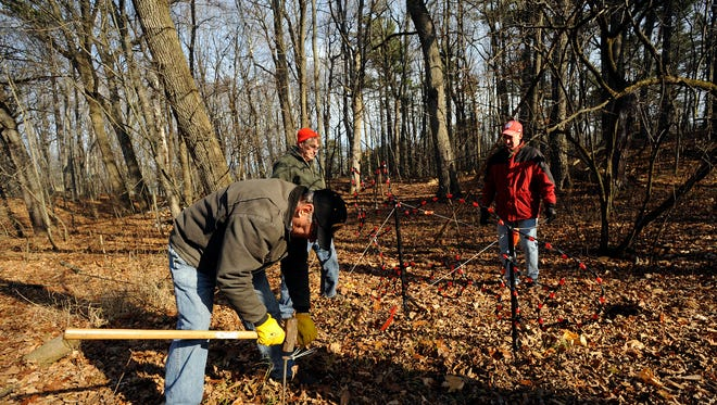 Volunteers (from left:) Bob Siehr, Jan Baetke, and Jerry Braun work on setting up lighted fixtures along the paths at Lincoln Park for the annual Lights At Lincoln fundraiser on Saturday, Nov. 15, 2014 at Lincoln Park in Manitowoc.  The drive-thru light show runs Nov. 28 through Dec. 27 from hours 5pm to 8 pm and costs $5 per vehicle. Proceeds from the fundraiser go toward improvements at the Lincoln Park Zoo. Matthew Apgar/HTR Media