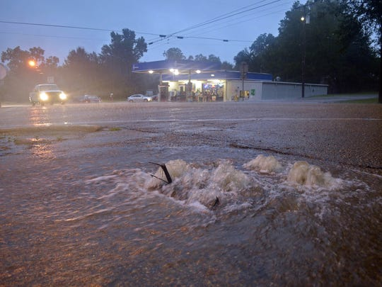 Floodwaters surge from a crack in the parking lot on