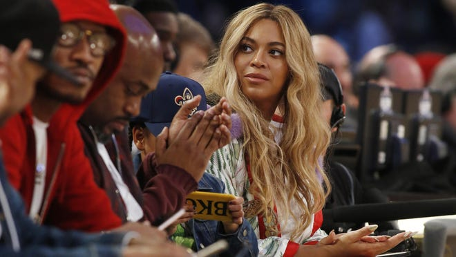 """FILE - In this Feb. 19, 2017. file photo, Beyonce sits at court side during the second half of the NBA All-Star basketball game in New Orleans. Netflix on Sunday, April 7, 2019 posted on its social media channels a yellow image with the word """"Homecoming"""" across it. The only other information was a date: April 17. That's when Netflix is expected to premiere a Beyonce special that may feature her performances at last year's Coachella Valley Music and Arts Festival. (AP Photo/Max Becherer, File)"""
