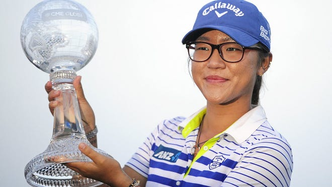 Lydia Ko of New Zealand holds up her Race to the CME Globe trophy on the 18 green Sunday, Nov. 23, at the Tiburon Golf Club at the Ritz-Carlton Golf Resort in Naples, Fla., after the final round of the LPGA's CME Group Tour Championship. Lydia Ko of New Zealand defeated Carlota Ciganda of Spain in a four-hole playoff.