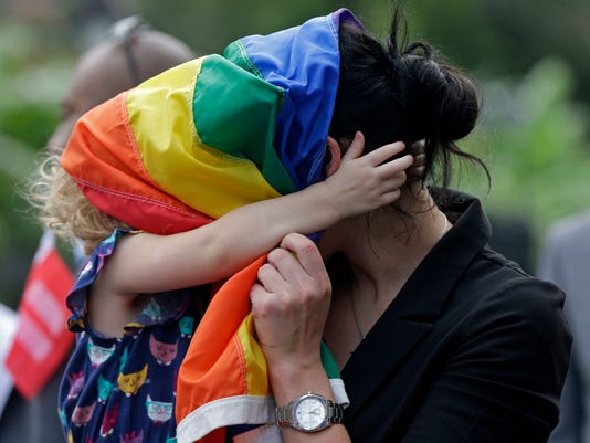 FILE - In this Sept. 3, 2014, file photo, Ariel David, of New Orleans, who is gay, plays with a pride flag wide with her biological daughter Nelly David, 2, during a rally held in reaction to a decision by a federal judge, which upheld Louisiana's ban on same-sex marriages, in New Orleans. David said she attended because she and her partner cannot legally marry in the state. New Orleans has long enjoyed a reputation in the South as a welcoming place for the lesbian and gay community. That reputation will be on display when the city hosts the NBA All-Star game next weekend. The game was awarded to New Orleans after the league decided to pull it from Charlotte last year. (AP Photo/Gerald Herbert, File)