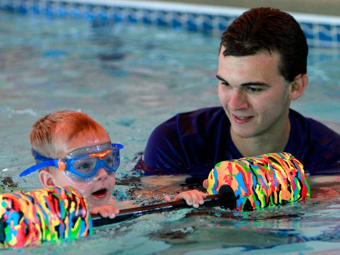 Swimming instructor Jacob Kerr works with 4-year-old Lucas Weis during swimming lessons at DiVentures Scuba & Swim Center.
