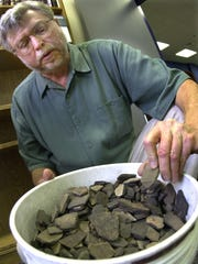 Former Historic Preservation Planner Tim Harrington arranges a basket of Indian pottery pieces, on loan to the city from a local collector of Old Fort Park artifacts in October 2003. The pottery is recorded in the first professional archaeological study of the park.