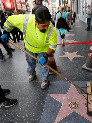 Eddy Giron cleans graffiti off the Bill Cosby star on the Hollywood Walk of Fame after it was defaced in Los Angeles on Friday. The Hollywood Chamber of Commerce wrote in a statement that it hoped people upset with Cosby would find different ways to express themselves than vandalism.
