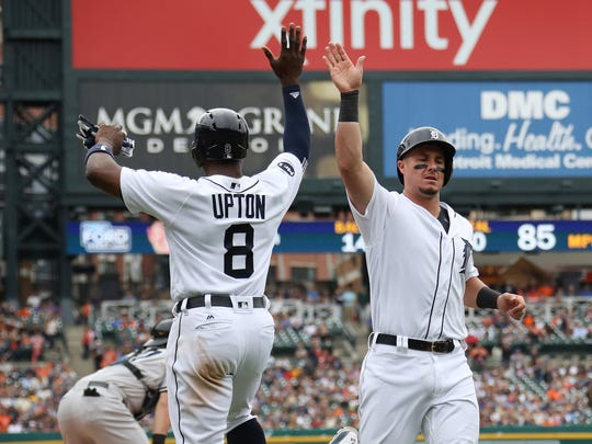 Tigers catcher James McCann celebrates scoring a fifth inning run with leftfielder Justin Upton during the Tigers' 10-6 win on Thursday, Aug. 24, 2017, at Comerica Park.