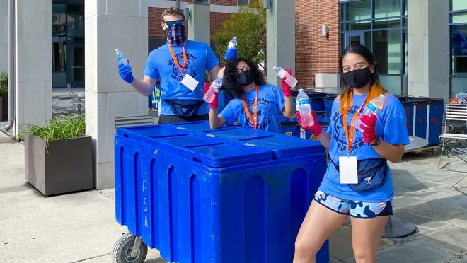 Drake Vineyard, Vanessa Barrara and Diana Ramirez hand out waters during move in at UAFS this week. This year the move in crew provided moral support, water and directions, but members were not permitted to load or carry items for students moving in, in an effort to minimize contact and prevent the spread of COVID-19.