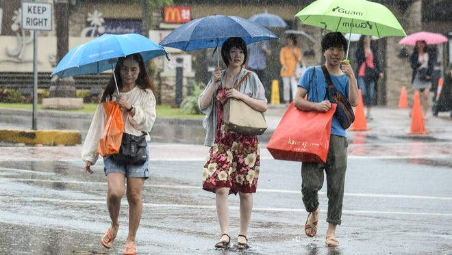 Pedestrians cope with a rainshower in Tumon on Thursday, Nov. 19.