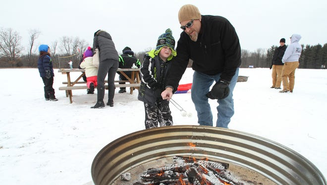 After a session on the nearby sledding hill, Earl Wakeman, right, shows son Erickson Wakeman, proper s'more marshmallow toasting techniques at the 2015 Hartland Family Winterfest.