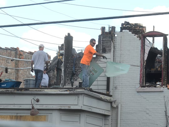 Workers begin to dismantle the upper level of the South Lyon Hotel, as they toss pieces of the building down to a container below on Aug. 22.