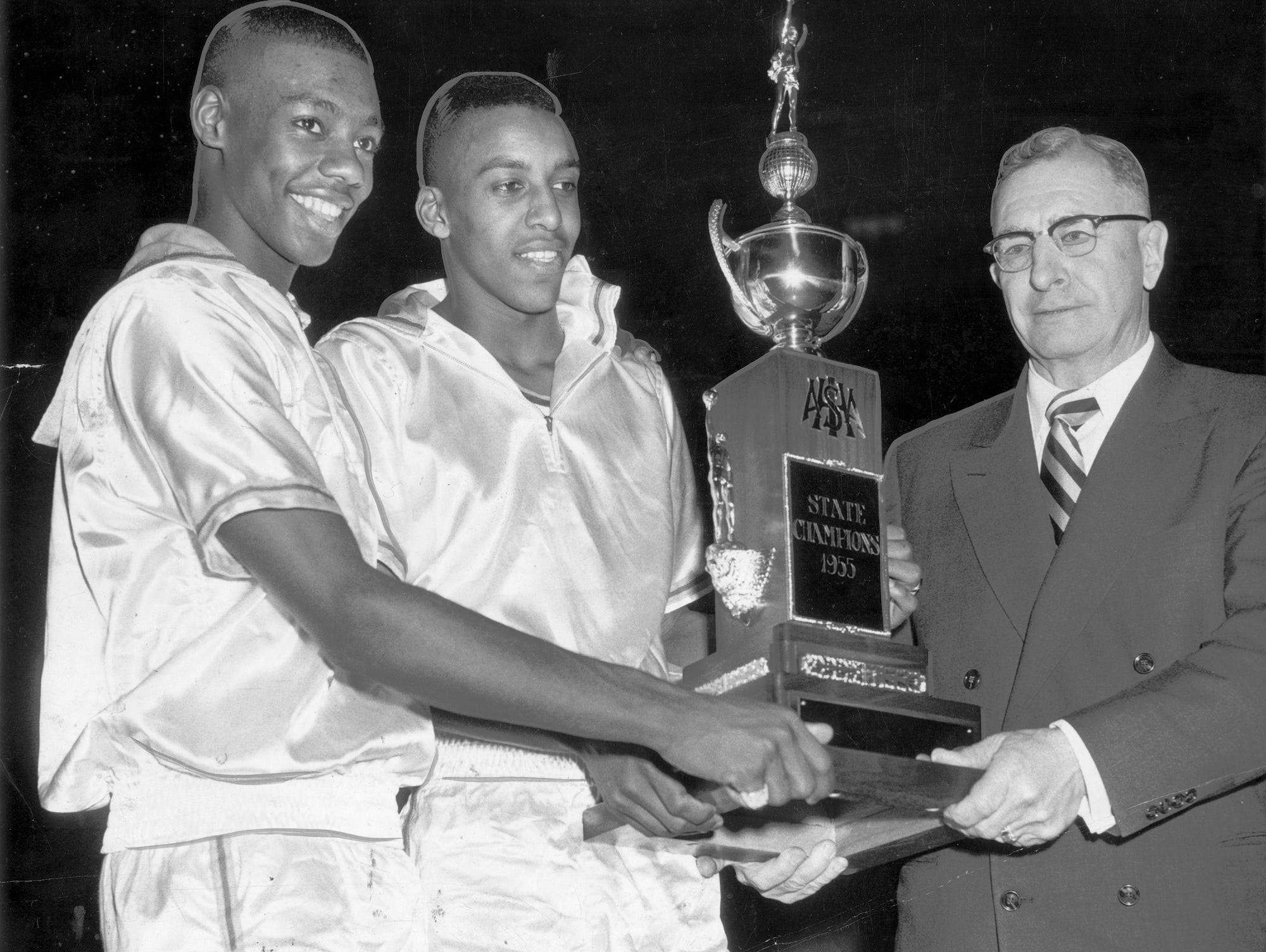 Oscar Robertson, left, and Willie Merriweather, co-captains of Attucks happily accept the state championship trophy from Otton Albright of Cayuga, president of IHSAA.