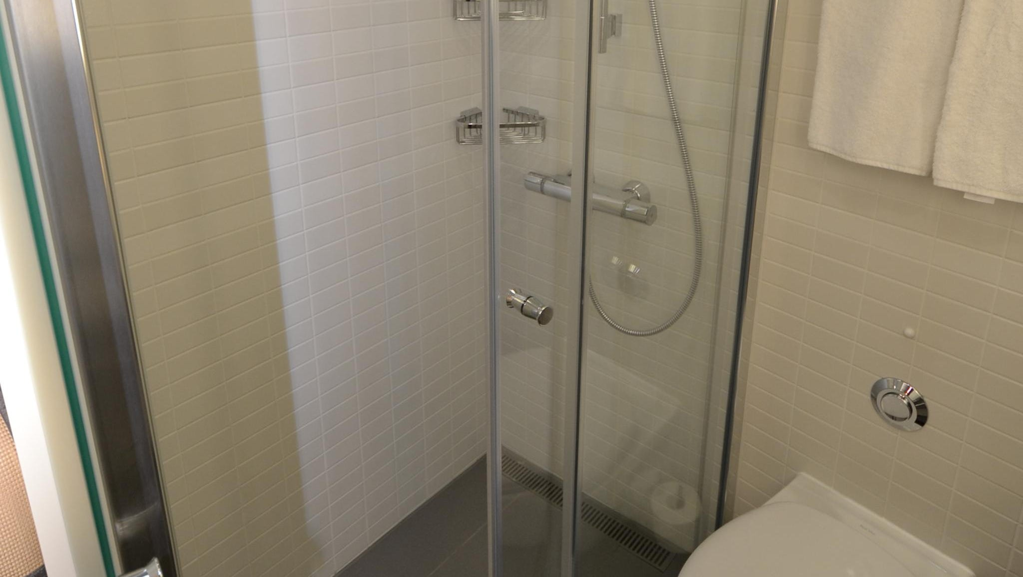 The bathrooms in French Balcony Staterooms feature a glass-enclosed shower area.