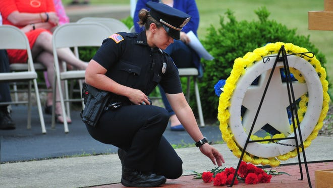 Officer Julia Shank places a flower near a memorial wreath in remembrance of an officer killed in the line of duty during the 2018 Peace Officers Memorial Service in Veterans Memorial Park.