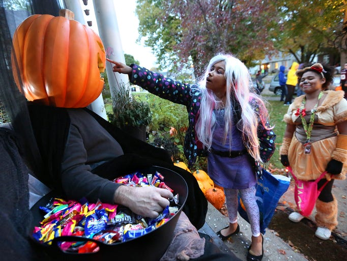 """Thaileah Winfrey, center, gets a closer look at Terry Kosel, dressed as the """"Great Pumpkin,"""" while trick-or-treating on Oct. 31on South Grandview Avenue in Dubuque, Iowa."""