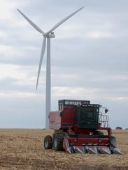 A combine in a field near the MinWind Energy windfarm