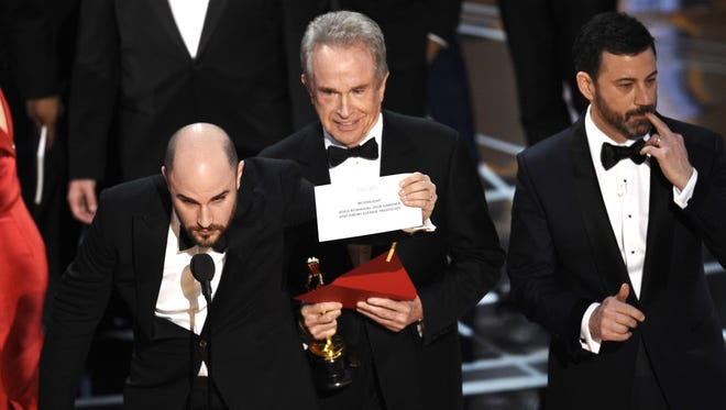 "'La La Land' producer Jordan Horowitz shows the envelope revealing ""Moonlight"" as the true winner of best picture at the Oscars, as presenter Warren Beatty and host Jimmy Kimmel look on."