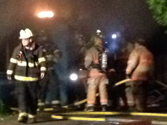 Firefighters work Tuesday as a flame is visible on