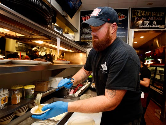 Kitchen Manager Johnny Williams is seen here as he prepares a food order at Texas Roadhouse in south Springfield on February 26, 2018.