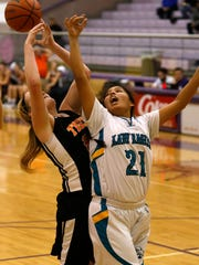Navajo Prep's Harlei Haceesa battles for a loose ball against a Grand Junction, Colo., player on Friday at Bronco Arena in Kirtland.