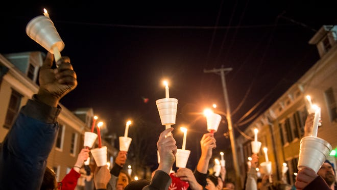 Walnut Street residents raise their candles Friday, March 23, 2018, at a neighborhood-organized vigil for Ivan Flanscha and Zachary Anthony, two York City firefighters who died in a building collapse nearby on Thursday. Assistant chief Greg Altland and firefighter Erik Swanson sustained injuries in the same collapse.