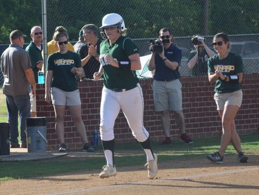 Holy Savior Menard softball coach Allison Frye (far right) applauds after Jensen Howell (20, left) hit a home run against Pope St. John Paul.