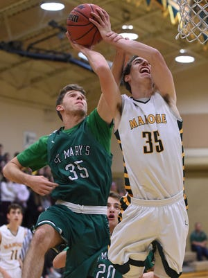 Bishop Manogue's John Reiley is fouled by St. Mary's Connor Tatum as he goes up to shoot at the Wild West Shootout at Bishop Manogue High School on Friday.