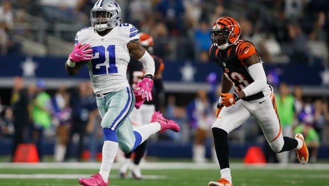 Dallas Cowboys running back Ezekiel Elliott (21) runs for a touchdown against Cincinnati Bengals free safety George Iloka (43) in the third quarter at AT&T Stadium.