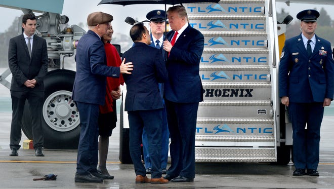 President Donald Trump is greeted on the tarmac at Los Angeles International Airport on Tuesday during his visit to California.