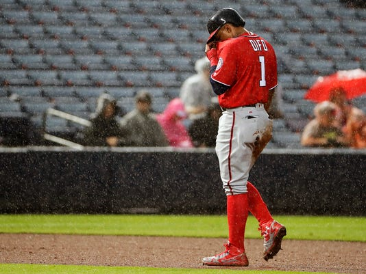 In the rain, Washington Nationals' Wilmer Difo returns to the dugout after being tagged out at second base on a force-out in the seventh inning of a baseball game against the Atlanta Braves in Atlanta, Sunday, Sept. 18, 2016. (AP Photo/David Goldman)