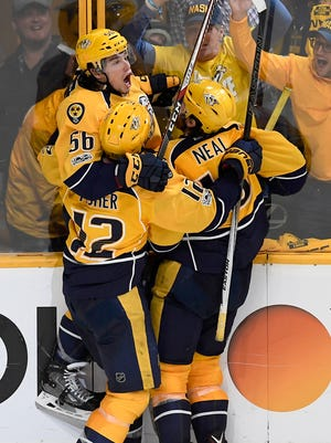 Predators left wing Kevin Fiala (56) is swamped by center Mike Fisher (12) and  right wing James Neal (18)  after scoring the game-winning goal in overtime to take the series to 3-0 in the first-round NHL playoff series late Monday night.