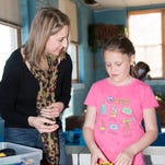 Jaime Mineart, left, assists in STEM focused activities at Imagination Station.