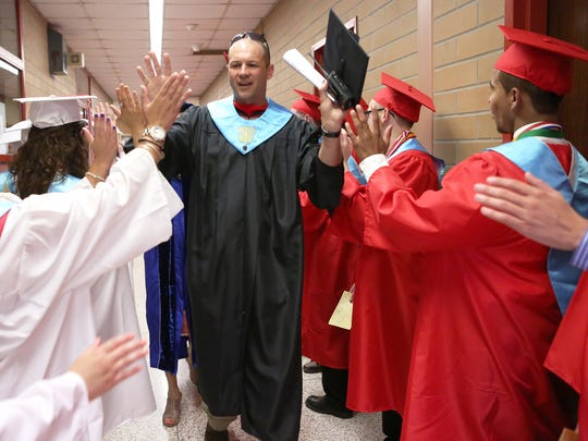 """Chairman for the graduation exercise Michael Siuta """"high fives"""" students as they are ready and geared up for the 2015 North Rockland High School graduation."""