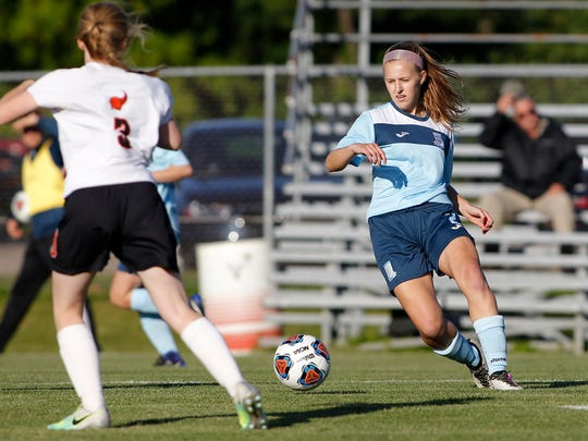 Lansing Catholic's Isabelle Poupard, right, moves the