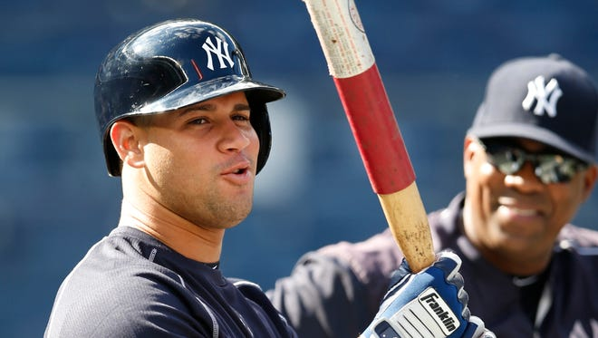 New York Yankees catcher Gary Sanchez, left, who was called up Wednesday, wields a weighted bat with assistant hitting coach Marcus Thames watching behind the batting cage before an interleague baseball game against the New York Mets, Wednesday, Aug. 3, 2016, in New York.