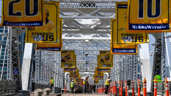 Workers contracted with the city power wash below banners of the Nashville Predators jerseys on the Shelley Foot Bridge in Nashville, Tenn., Tuesday, April 10, 2018.
