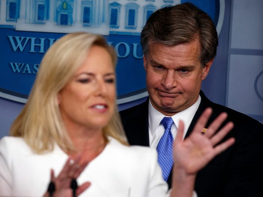 FBI Director Christopher Wray listens as Secretary of Homeland Security Kirstjen Nielsen speaks during the daily press briefing at the White House Aug. 2, 2018, in Washington.