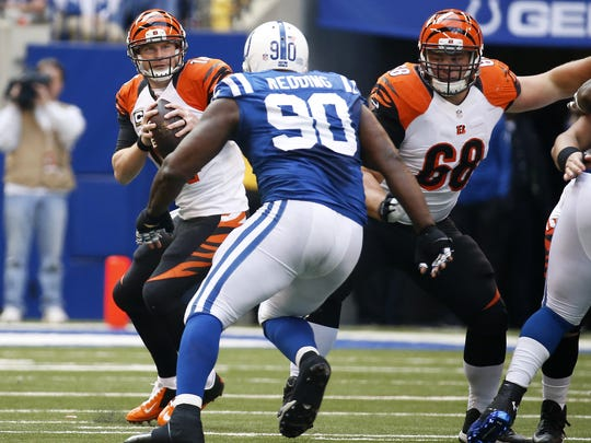 Cincinnati Bengals quarterback Andy Dalton (14) looks to avoid the pressure by the Indianapolis Colts defensive end Cory Redding (90) at Lucas Oil Stadium.