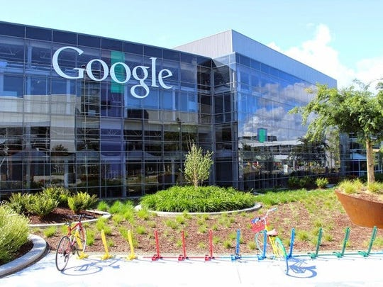"""Glass-walled, multistory Googleplex with """"Google"""" written on side of building and a couple bikes in multicolor bike racks in foreground"""