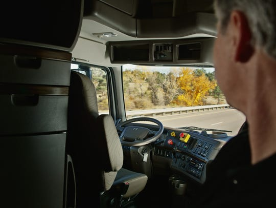 An Otto truck driver watches the wheel from the cab