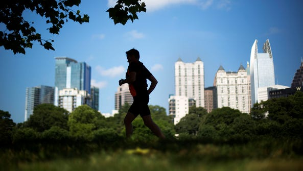 A jogger runs along a path in Piedmont Park as the