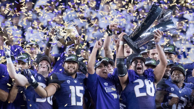 The Washington Huskies celebrate their victory in the Pac-12 championship game last December in Santa Clara, Calif. The preseason 2017 media poll makes the Huskies a favorite the return to the game this winter.