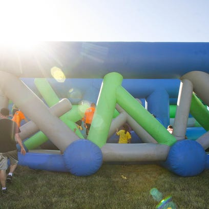Participants maneuver their way through one of 11 obstacles at the Insane Inflatable 5K at Hope Sports Complex in Lansing August 1.