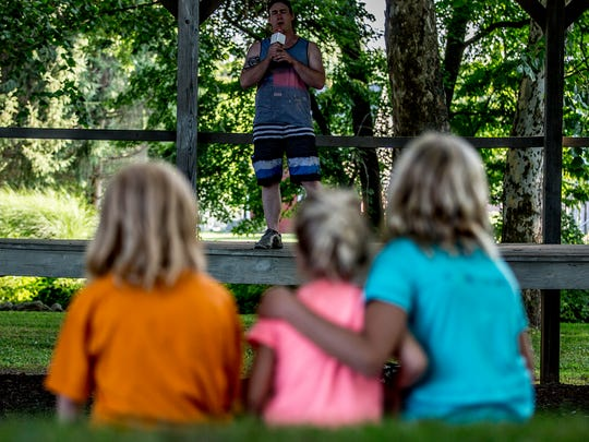 Taran Martin, 25, sings on the outdoor stage at the River View Community Park while Amber Nelson, Skylar Nelson and Katie Walser watch. Martin was the opening act of a talent show sponsored by Katie's Wacky World YouTube Channel.