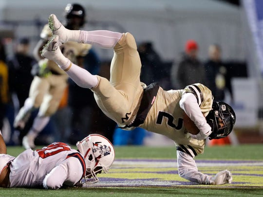 Whitehaven High School wide receiver Markerion Johnson (2) falls over Oakland High School linebacker Brandon Turner (20) during the first half of the Division I Class 6A Tennessee high school football championship game Saturday, Dec. 3, 2016, in Cookeville, Tenn.
