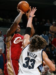 The Cavaliers' LeBron James (23) shoots a 3-pointer over the Grizzlies' Mike Miller (33) during a 2008 game.