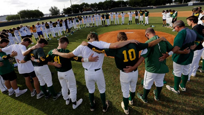 Baseball players from Santa Fe High School and Kingwood Park High School come together around the pitching mound to say a prayer before their game in Deer Park, Texas, on May 19, 2018.