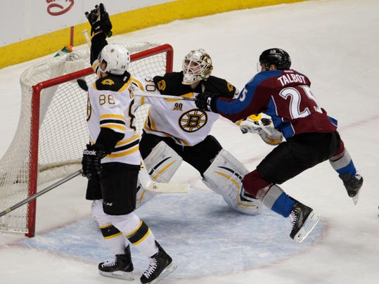 Boston Bruins defenseman Kevan Miller (86) catches the puck as Colorado Avalanche center Maxime Talbot (25) hops toward it against Boston Bruins goalie Chad Johnson (30) the first period of an NHL hockey game in Denver on Friday, March 21, 2014.(AP Photo/Joe Mahoney)
