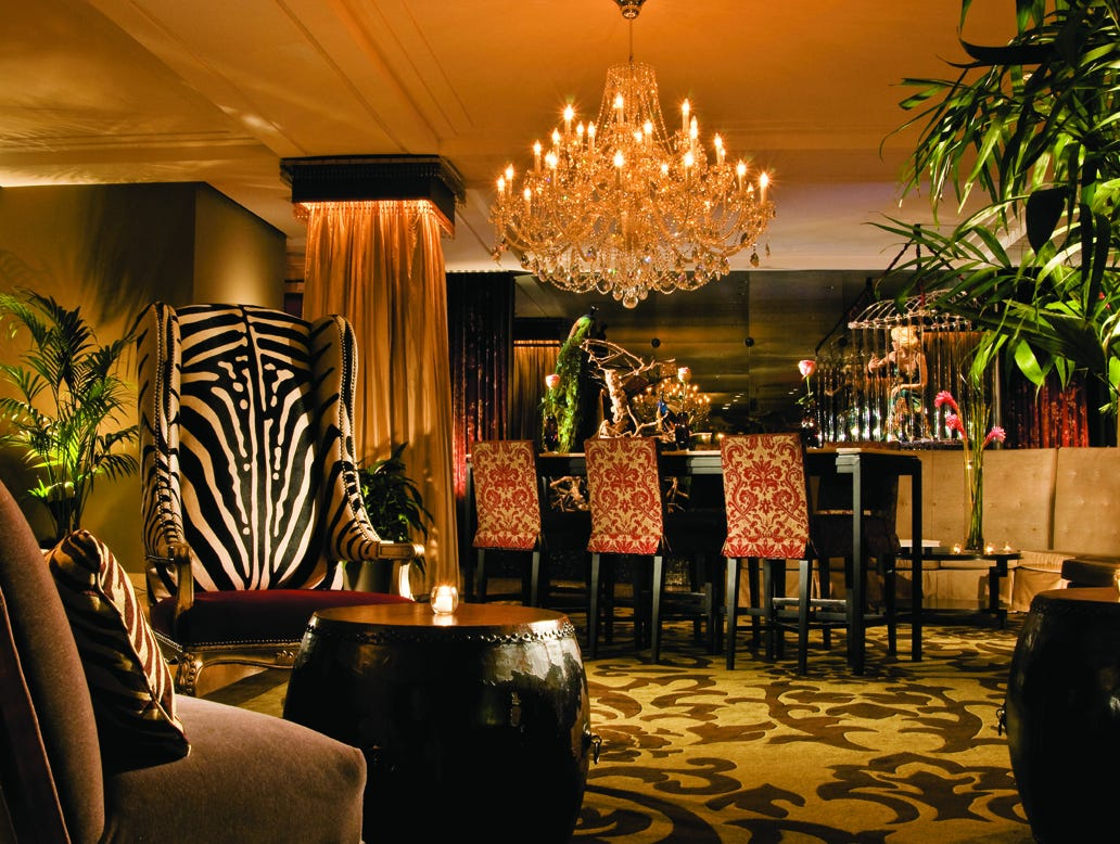 Wild touches, like animal-print chairs, bold carpet patterns and a cage in the background, bring a different world to life at Hotel ZaZa in Houston.