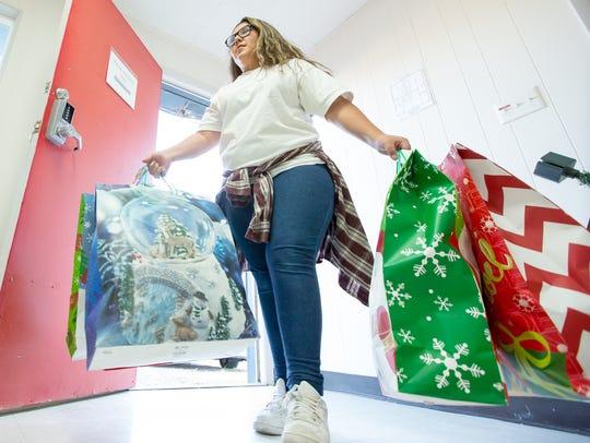 Zadie Fernandez, 12, of Las Cruces, carries holiday