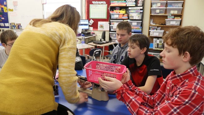 Jamie Melos helps students Logan Kibby, Caleb Casey and Brendon Ryan weigh the class tortoise as part of their math class at Merton WIlliams Middle School in Hilton.