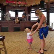 Kaylee Malone and her daughter, Maycee Stolsig, 2, dance to the music of the David & Joe Trio opening Jamaican Fest on Friday through the rest of the weekend at Bamboo Willie's on the Portofino Boardwalk on Quietwater Beach.